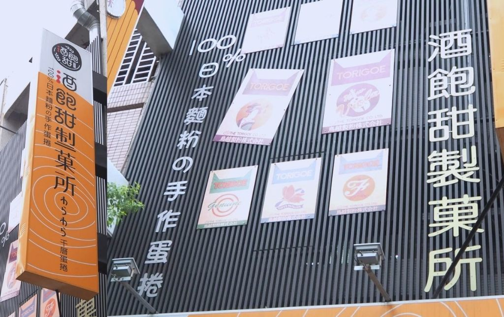 沒有賣酒的酒飽甜,只賣千層蛋捲?抬頭一看,招牌牆上掛著酒飽甜製菓所的日本麵粉袋